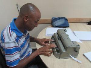 Descrição da Imagem: Um homem sentado, ele está escrevendo em uma máquina Perkins, máquina de escrever em braille. Fim da descrição
