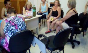 seis mulheres sentadas em volta de uma mesa, onde estão dispostos lanches e bebidas para confraternização no grupo de convivência