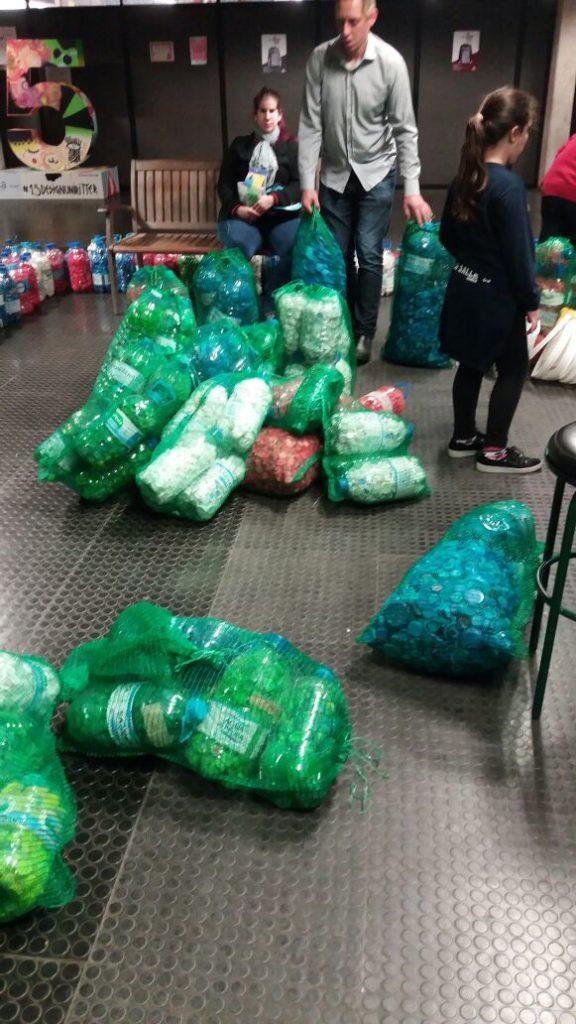 Descrição da imagem: Várias tampinhas plásticas dentro de garrafas de água de 5 litros. As garrafas estão ensacadas. Em casa saco tem 5 garrafas cheias de tampinhas. Em pé um homem carregando dois sacos cheios de tampinhas. Fim da descrição.