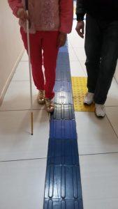 Descrição da imagem: foto em orientação retrato enquadra as pernas de duas pessoas que estão lado a lado. A mais a esquerda possui uma bengala longa que tateia um piso tátil em seu caminho.Fim da descrição.