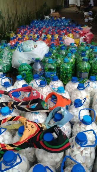 Descrição da imagem: foto destaca dezenas de garrafas de 5 litros de água com muitas tampinhas plásticas dentro. Fim da descrição