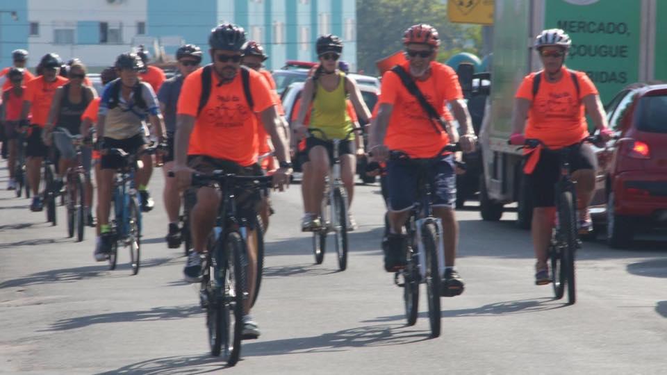 Descrição da imagem: foto em orientação paisagem destaca grupo de ciclistas pedalando pela via. A maioria deles utilizam camisetas laranja e estão em bikes de dois lugares. Fim da descrição