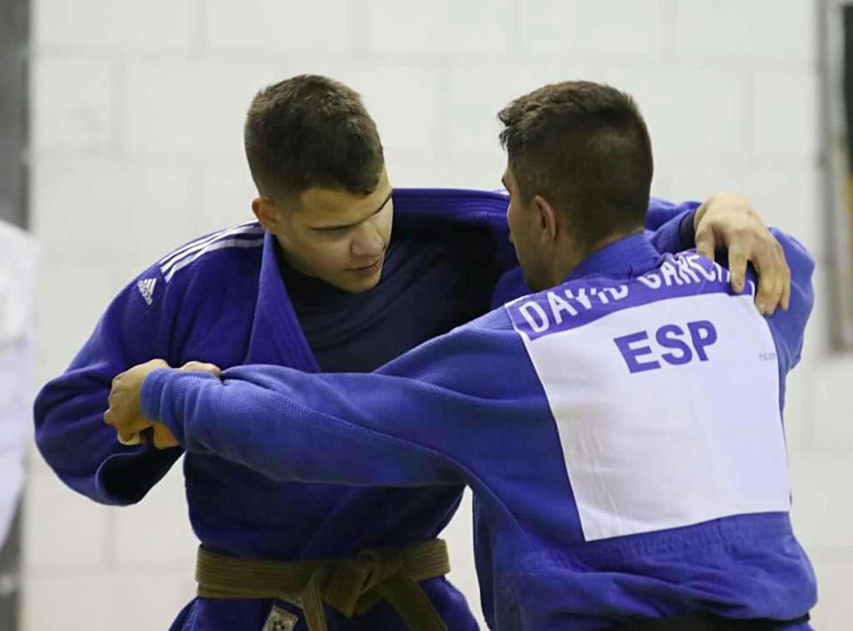 Descrição da imagem: Foto em orientação paisagem destaca Judoca Anderson Wassian em treino com o judoca David Garcia da Espanha. Os dois atletas estão em pé e usam kimonos azuis. Eles travam disputa de pegada. Fim da descrição.