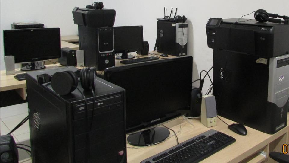 Descrição da Imagem: foto em orientação paisagem destaca computadores e periféricos na cor preta que Estão Sobre uma mesa clara. Fim da descrição.