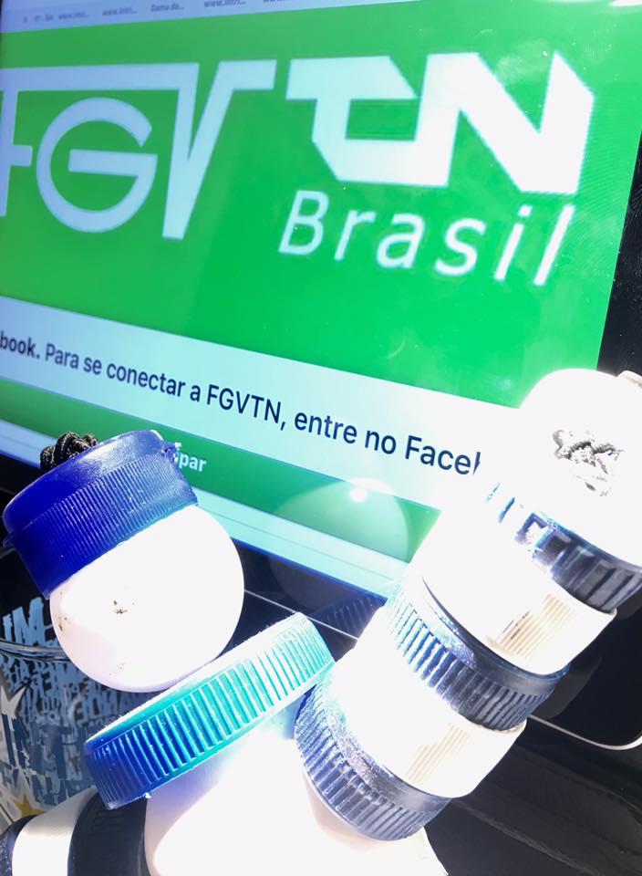 Descrição da imagem foto orientação retrato destaca o mascote Acerguito. Ele é feito de tampinhas brancas e azuis e está na base da foto com o braço esquerdo levantado em comemoração. Sobre sua cabeça a marca da FGTN, fundo verde letra branca. Fim da descrição.