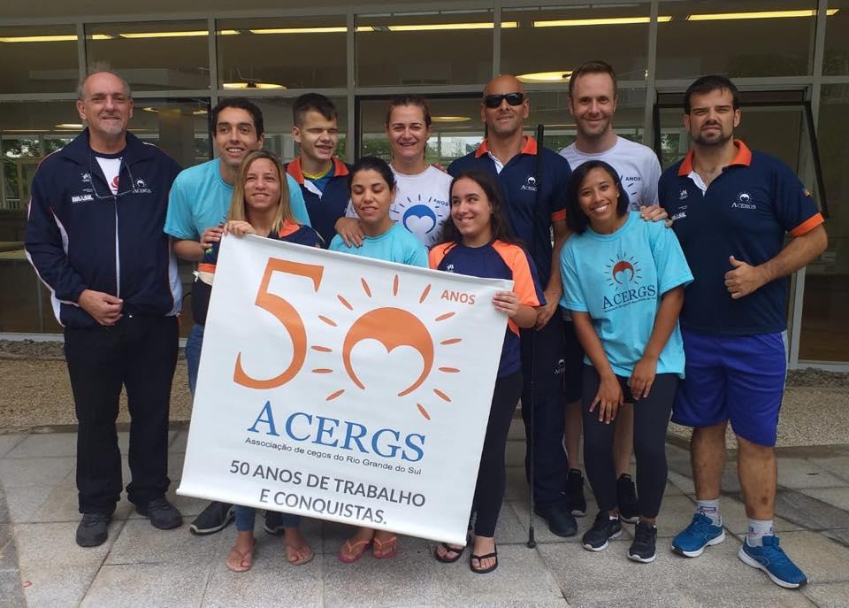 Descrição da imagem: Foto em orientação paisagem destaca a equipe da ACERGS/UFRGS de Judô reunida para foto no pátio do CT Paralímpico. Os atletas seguram o banner da instituição. Fim da descrição.