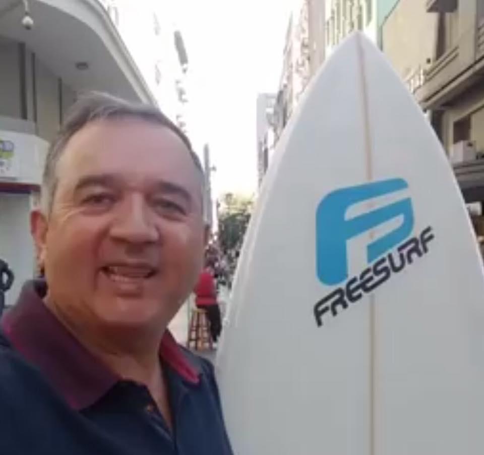 Descrição da imagem: foto destaca um homem branco com uma prancha em pé a o seu lado direito. Fim da descrição.