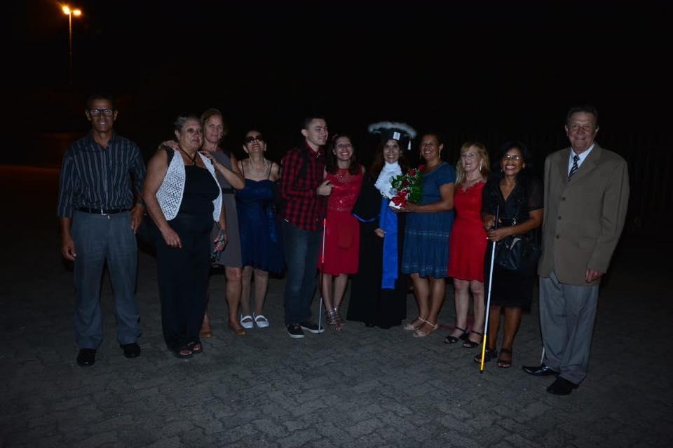 Descrição da imagem: foto orientação paisagem destaca grupo de pessoas em pé, vestidas a caráter e posando para a foto. Em meio ao grupo uma mulher veste uma toga de formanda. Fim da descrição.