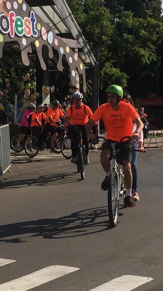 Descrição da imagem: Foto em orientação retrato destaca ciclistas de camisetas cor laranja com logo Pedal da ACERGS na altura do peito. Eles pedalam bicicletas duplas e ao fundo e no alto o pórtico da ChocoFest. Fim da descrição.