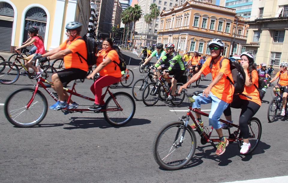 Descrição da imagem: foto em orientação paisagem destaca duas duplas de ciclistas com camisetas laranjas em bicicletas de dois lugares trafegando pela Av. Júlio. de Castilhos próximo ao mercado público. Ao fundo demais ciclistas pedalando em acompanhamento. Fim da descrição.