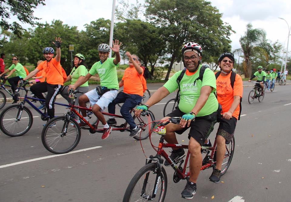 Descrição da imagem: foto em orientação paisagem destaca três duplas de ciclistas em bicicletas de dois lugares. Eles pedalam e acenam para a foto. Fim da descrição.