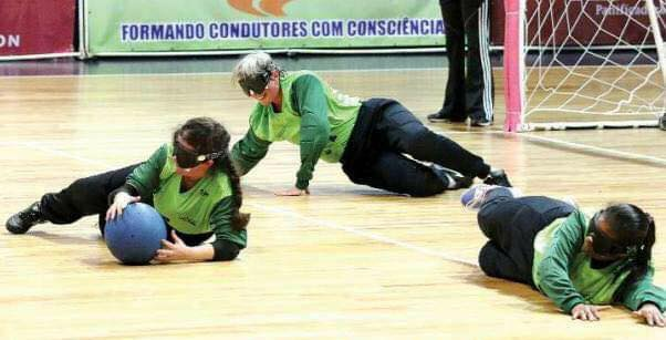 Descrição da Foto: Imagem em orientação paisagem. Três atletas do time feminino da ACERGS de uniforme verde estão deitadas na posição de defesa e a jogadora do cetro (pivô) está com a bola de cor azul, apostar feito defesa. Fim da descrição.
