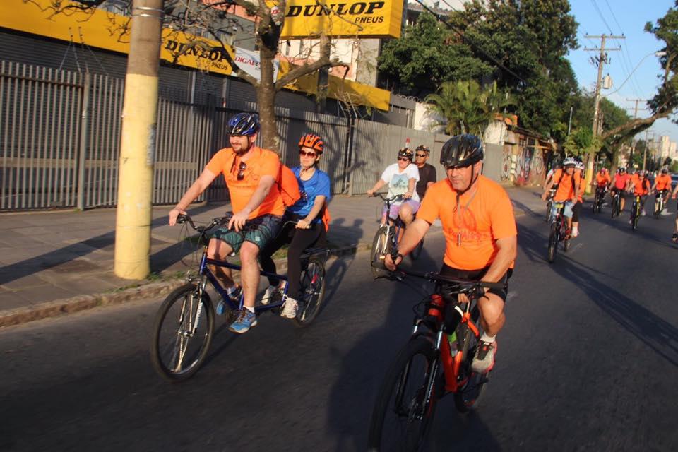 Descrição da imagem: foto orientação paisagem destaca grupo de ciclistas alinhado em uma faixa de via pública. Eles estão em bicicletas duplas e usam predominantemente camisetas laranja. Fim da descrição
