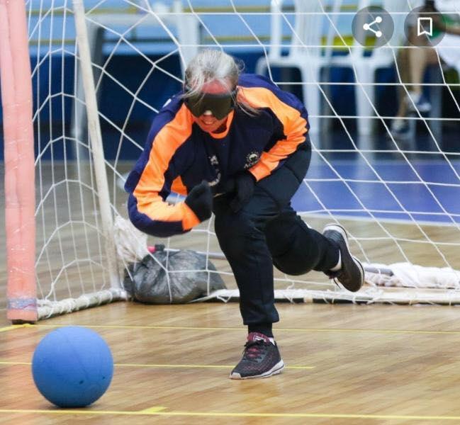Descrição da Foto: Imagem em orientação paisagem. Na foto aparece a atleta Idalina Raquel no momento em que lança a bola em direção ao seu adversário.