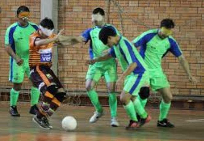 Descrição da imagem: foto em orientação paisagem apresenta situação de defesa de jogo em que quatro jogadores da ACERGS, com uniformes verdes com detalhes azuis claro, cercam um jogador adversário que conduz a bola. Fim da descrição.