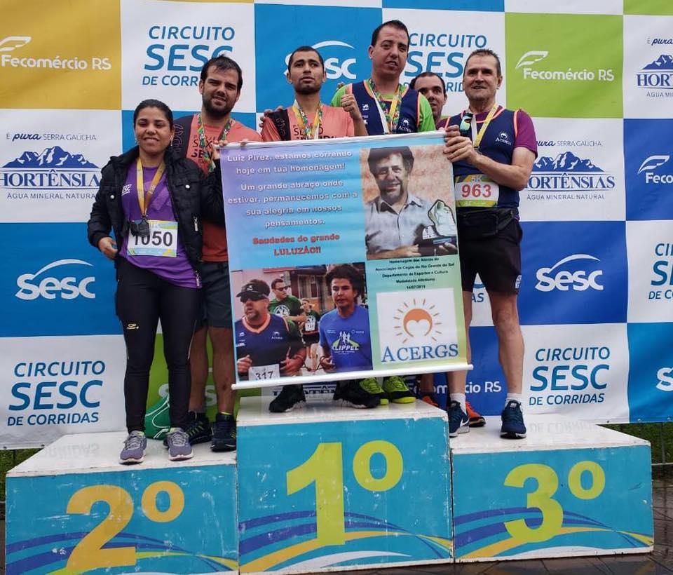 Descrição da Imagem: Foto em orientação paisagem. Atletas da ACERGS reunidos no pódio seguram o banner com homenagem ao atleta Luiz Elmer Pires. Fim da descrição.