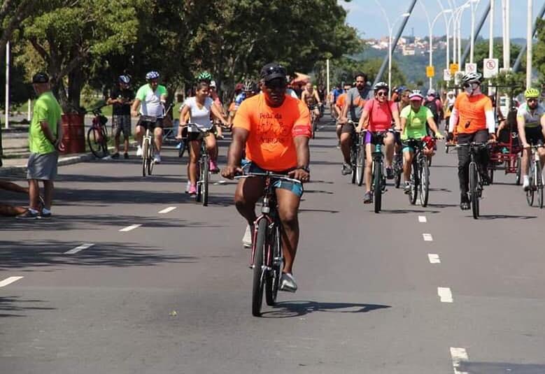 Descrição da imagem: foto em orientação paisagem destaca dezenas de ciclistas pedalando e ocupando toda a via de uma rua arborizada. Fim da descrição.