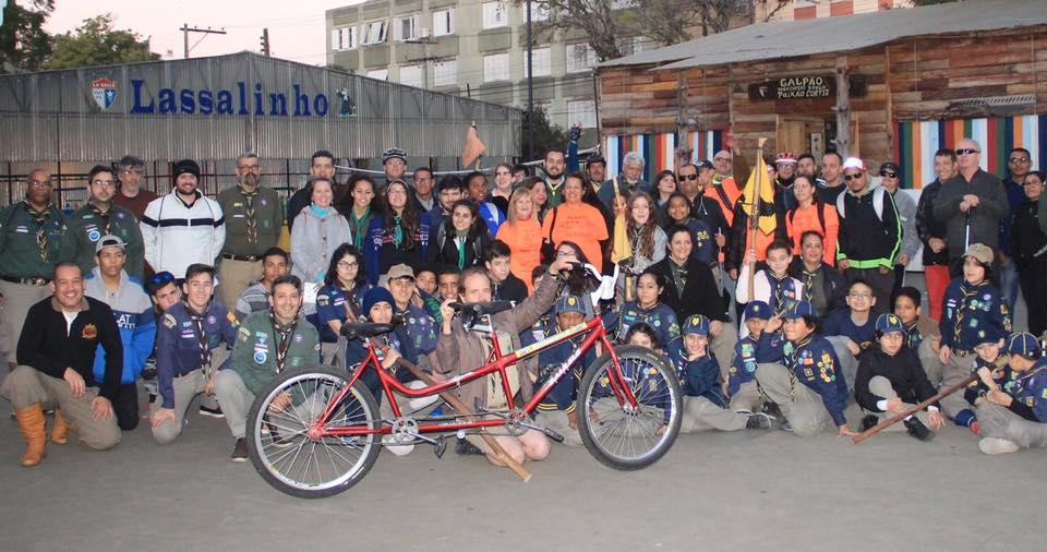 Descrição da imagem: foto em orientação paisagem destaca grupo de ciclistas e escoteiros posando para foto com uma bicicleta de dois lugares tanden a frente. Fim da descrição.