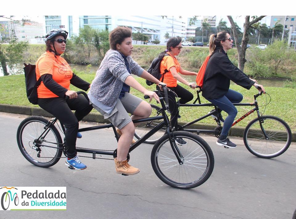 Descrição da imagem: foto destaca quatro ciclistas em duas bicicletas de dois lugares. Sobre cada uma estão 2 mulheres brancas.