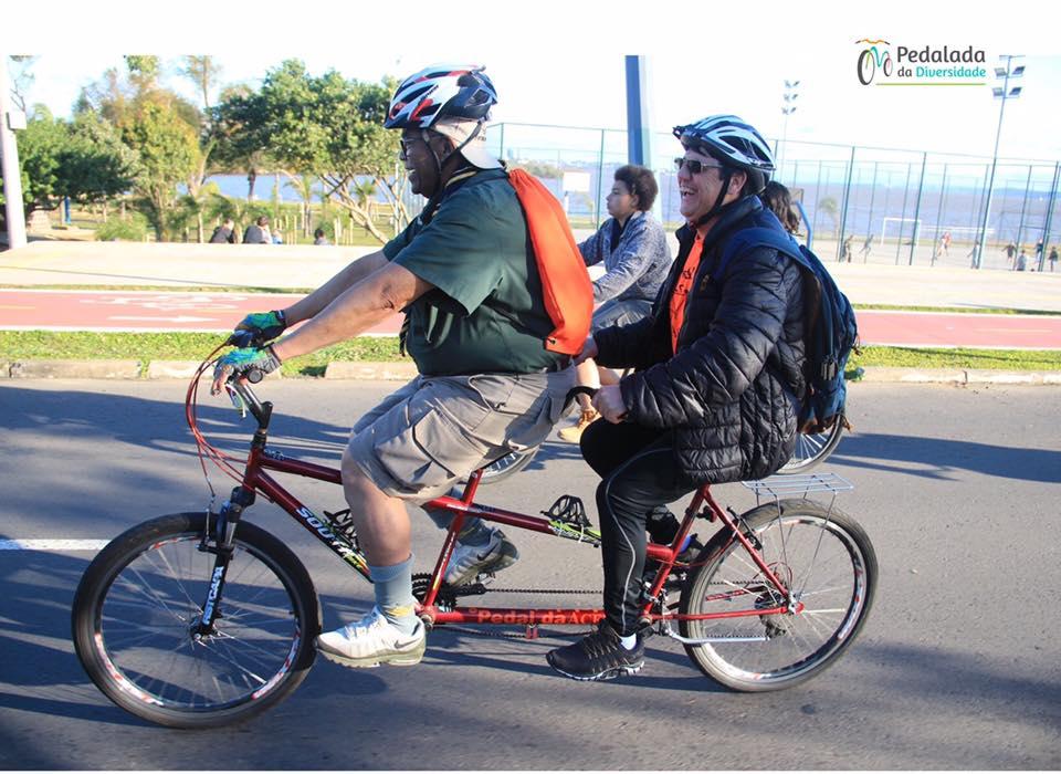 Imagem destaca-se uma dupla de ciclistas em uma bicicleta de dois lugares o guia é negro e conduz uma pessoa com deficiência visual branca. Fim da descrição.