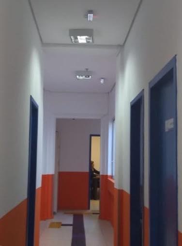 DESCRIÇÃO DA IMAGEM: foto na vertical destaca corredor de acesso às dependências da ACERGS. As paredes estão pintadas de branco e possuem faixa alaranjada na horizontal que percorre todo o corredor, e localizadas no terço baixo das paredes. As portas, 3, na cor azul contrastam com as demais cores e se visualiza piso TATIL azul . Fim da descrição.
