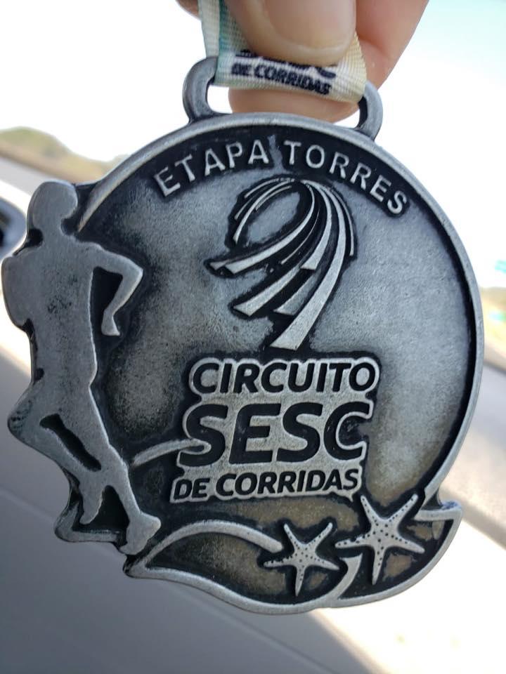 Descrição da imagem: foto em orientação paisagem apresenta a medalha da corrida, que destaca em alto relevo a silhueta de um corredor, ondas, estrelas-do- mar, e a logo do Circuito SESC-RS de corridas. Fim da descrição.