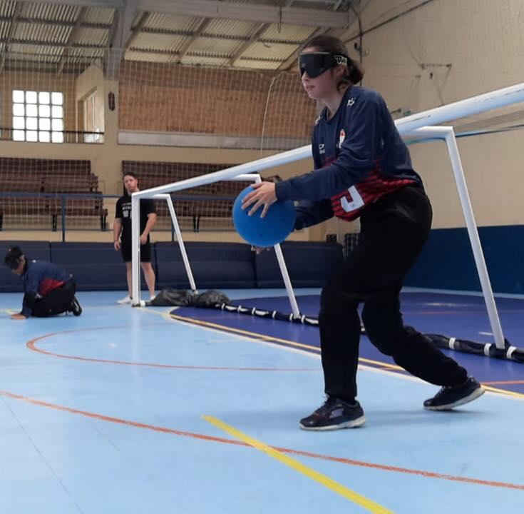 Descrição da foto: Imagem em orientação paisagem apresenta uma atleta Camila Pacheco da equipe feminina da ACERGS. Ela segura a bola em preparação para atacar o gol adversário. Fim da Descrição.