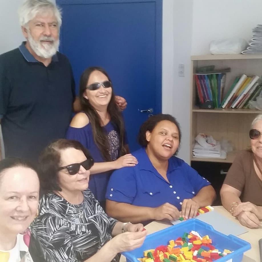 Descrição da imagem: Foto em orientação paisagem com 6 pessoas.  Todos estão sorrindo e algumas delas, estão manuseando as peças de lego. Fim da descrição.