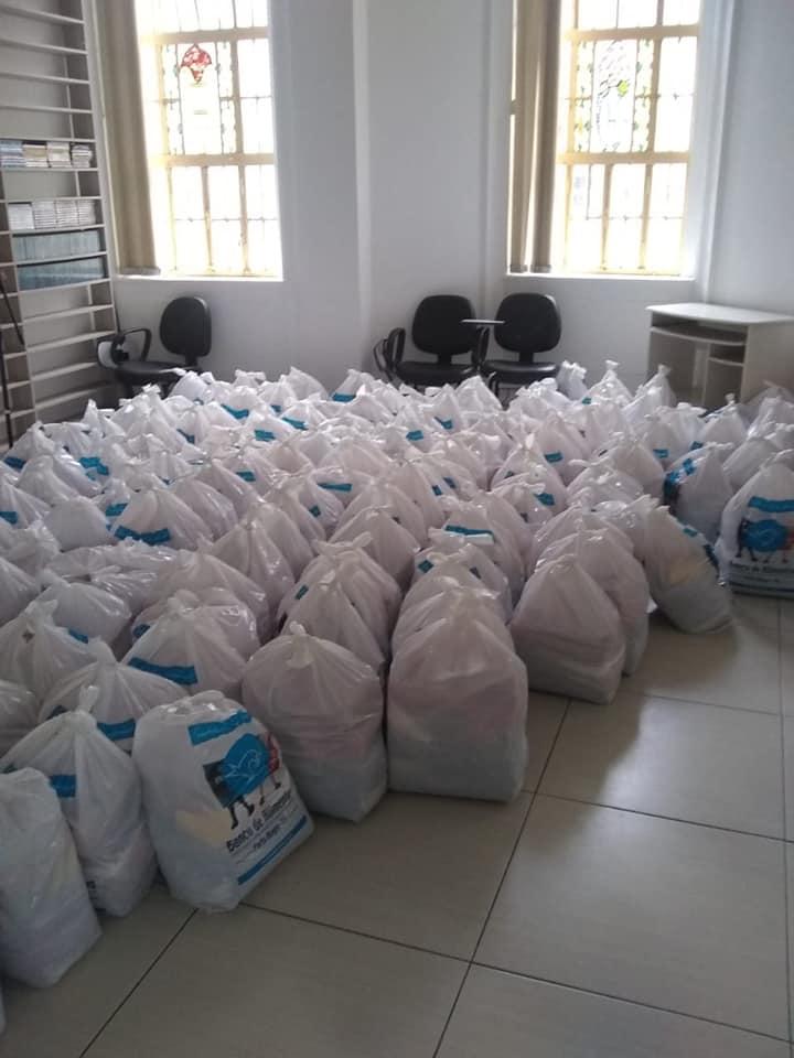 Descrição da imagem: foto de salão com dezenas de sacolas brancas de cestas básicas ao chão. Fim da descrição