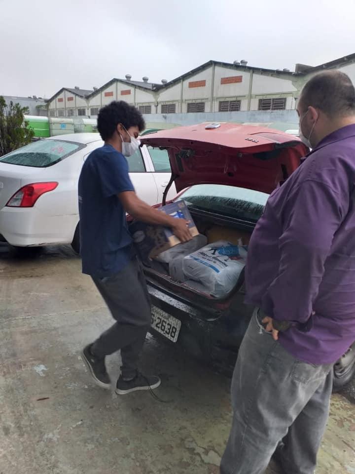 Descrição da imagem: pessoa carregando um fardo de caixas de leite com porta malas de carro aberto à sua frente Fim da descrição