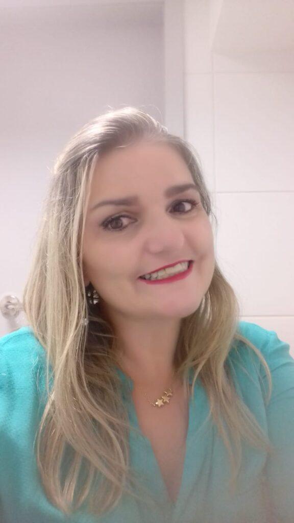 Descrição da imagem: A candidata tem cabelos loiros um pouco abaixo dos ombros, veste uma blusa azul clara, Está sorrindo. Fim da descrição.
