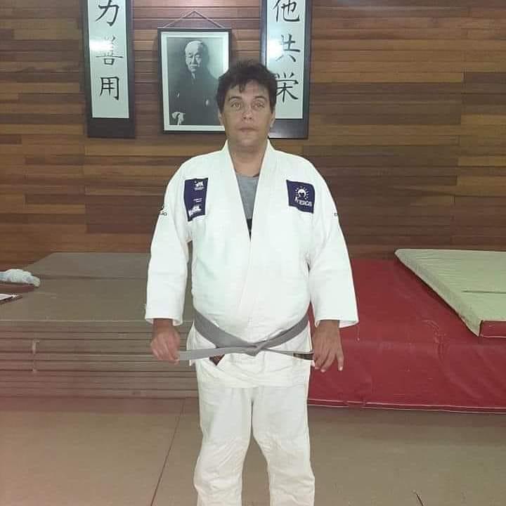 Descrição da imagem: Foto do Thiago, ele está vestindo um quimono branco e segura as pontas da sua faixa cinza, Thiago está em pé dentro do Dojo. Ao fundo a foto do Sansei Jigoro Kano. Fim da descrição.