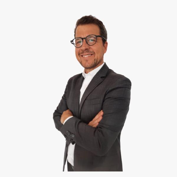 Descrição da imagem: Homem de pele clara, cabelos castanhos claros, usa óculos e está sorrindo de braços cruzados. Está vestindo um blazer preto e uma camisa social branca. Fim da descrição